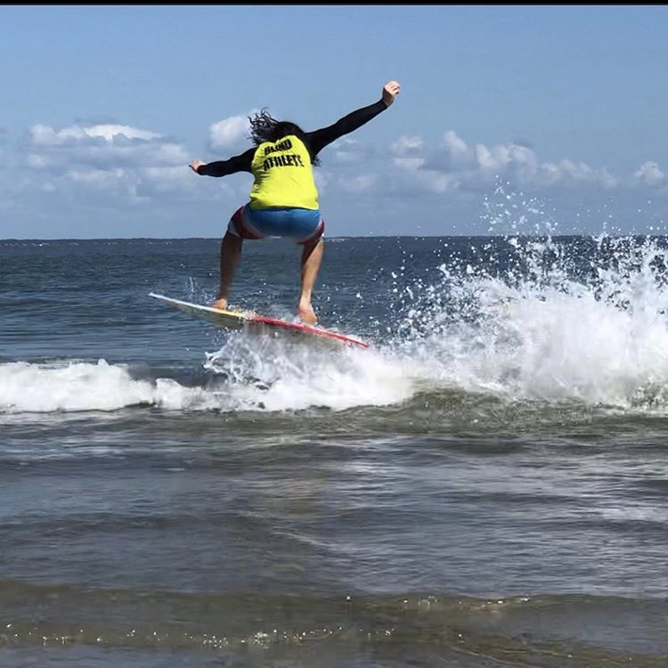 "An image of Kai skimboarding and catching air off the waves. He's wearing a jersey which reads ""Blind Athlete"" across the back."